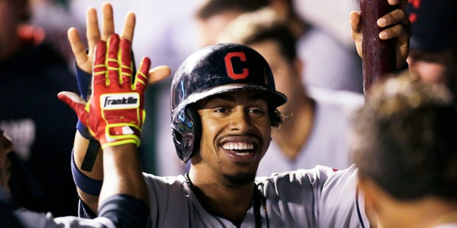 FILE - In this Sept. 30, 2016, file photo, Cleveland Indians' Francisco Lindor is congratulated in the dugout after scoring during the third inning of a baseball game against the Kansas City Royals at Kauffman Stadium in Kansas City, Mo.  While most of America gushes over the Chicago Cubs and their quest at ending a 108-year World Series drought, Cleveland's taking aim at its own championship dryspell following a season in which the Indians overcame numerous obstacles and outclassed the AL Central. (AP Photo/Colin E. Braley, File)