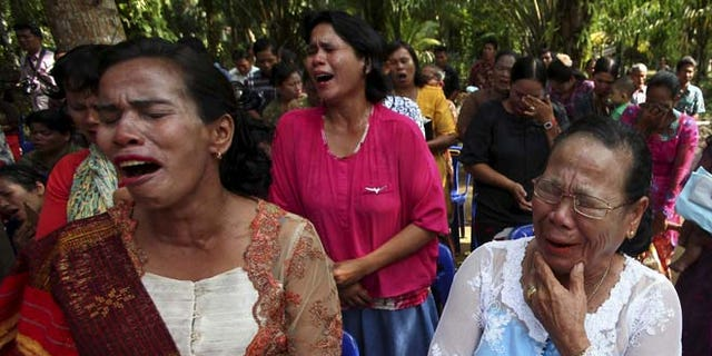 Oct. 18: Residents cry as they attend a Sunday mass prayer near a burned church at Suka Makmur Village in Aceh Singkil.
