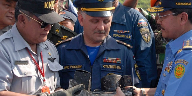 May 16, 2012: Chief of Indonesian National Transportation Safety Board Tatang Kurniadi, left, National Search and Rescue Agency head Daryatmo, right, and an unidentified Russian investigator inspect the burnt cockpit voice recorder of a Sukhoi Superjet-100.