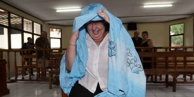 Jan. 3, 2013: Lindsay June Sandiford of Britain, covers her face from the camera as she sits in the dock during her trial.