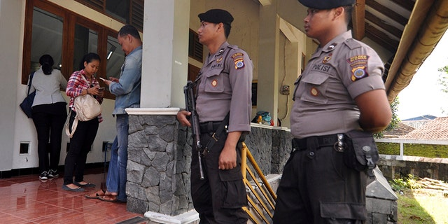 Police officers stand guard outside St. Lidwina Church following an attack in Sleman, Yogyakarta province, Indonesia, Sunday, Feb. 11, 2018. Police shot a sword-wielding man who attack the church during a mass, injuring a number of people including a German priest. The reason for the attack Sunday morning was not immediately clear. (AP Photo/Slamet Riyadi)