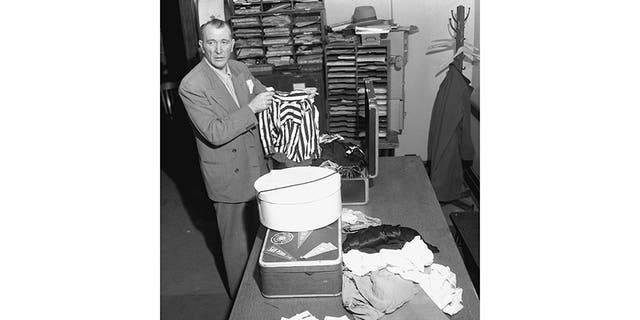 """Det. Sgt. Bill Cummings inspects the contents of Elizabeth's suitcase and hatbox, checked into the Greyhound bus station when she was with Robert """"Red"""" Manley."""