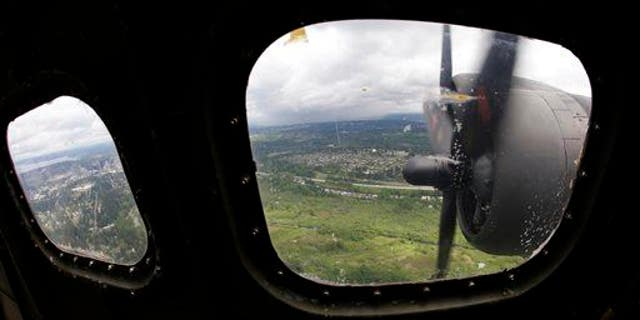 """Two of the four engines of a Boeing B-17 """"Flying Fortress"""" bomber are shown through a window May 5, 2014, as it flies near Seattle."""