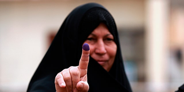 An Iraqi woman shows her ink-stained finger after casting her vote in the country's parliamentary elections in Ramadi, Iraq.