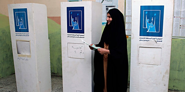 An Iraqi woman prepares to casts her vote in the country's parliamentary elections in Basra.