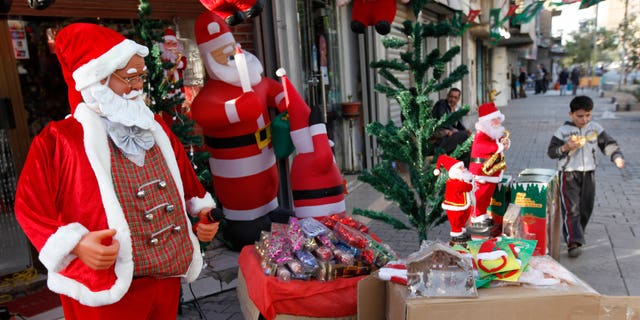 Dec. 22: A boy walks past a shop selling Christmas decorations in downtown Baghdad, Iraq. Church officials in Iraq say they have canceled some Christmas festivities in two northern cities over fears of insurgent attacks.