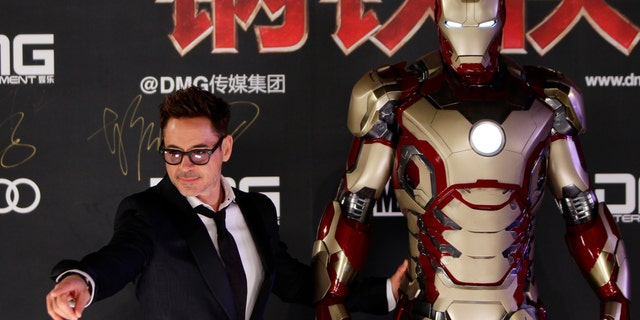 """Cast member Robert Downey Jr. poses for a photo with an Iron Man figure during a promotional event of the movie """"Iron Man"""" April 6, 2013."""