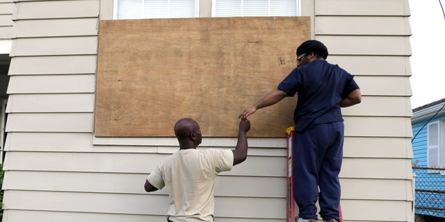 Aug. 28, 2012: Stacey Davis, left, hands a screw to his son as they board up windows on their home before Hurricane Isaac hits in New Orleans.
