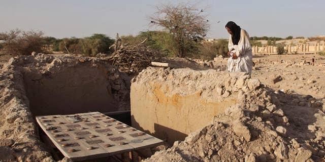 A mausoleum caretaker prays at a damaged tomb in Timbuktu, in 2014.