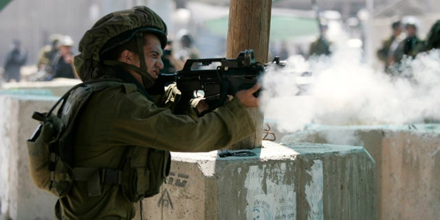 Aug. 26, 2011: An Israeli soldier fires tear gas canisters at Palestinian protesters during a protest march at the Qalandia checkpoint between the West Bank city of Ramallah and Jerusalem.