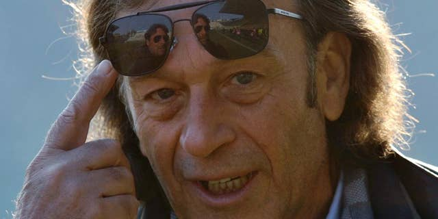 FILE - A Sunday, Dec. 15, 2013 photo from files of the then Cagliari president Massimo Cellino gesturing prior to the Serie A soccer match between Parma and Cagliari at Parma's Tardini stadium. Massimo Cellino _ with his sunglasses and slick, graying hair _ breezed into Elland Road in April when his company, which already owned Italian side Cagliari, bought a controlling stake in Leeds. This was the biggest football team in England in the late 1960s and early '70s in the era of Johnny Giles and Billy Bremner, the league champion in 1992 when Eric Cantona starred up front and a Champions League semifinalist only 12 years ago. (AP Photo/Marco Vasini, File)