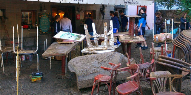 Oct. 26, 2011: Mud covered tables are seen stacked outside a bar in Monterosso, Italy.