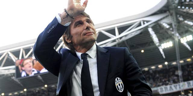 FILE - In this April 7, 2014 file photo, Juventus coach Antonio Conte waves to supporters during a Serie A soccer match between Juventus and Livorno at the Juventus stadium, in Turin, Italy. On Tuesday, July 15, 2014 Juventus and Conte announced the coach's contract terminated by mutual consent. (AP Photo/Massimo Pinca, files)