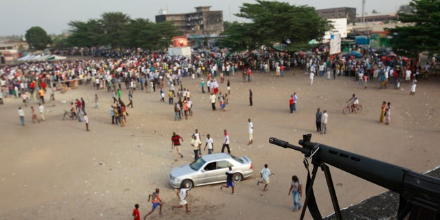 Jan. 5, 2011: A sniper stands guard over a public square ahead of the arrival of Charles Ble Goude, a youth leader recently named to Laurent Gbagbo's cabinet who is staging rallies in support of the incumbent president, in the Koumassi neighborhood of Abidjan, Ivory Coast. While the United Nations and other world powers recognize rival Alassane Ouattara as the winner of November presidential elections, Gbagbo has refused to step down for more than a month after the presidential runoff vote. The 15-nation regional bloc ECOWAS has threatened to remove the incumbent leader if ongoing negotiations fail.