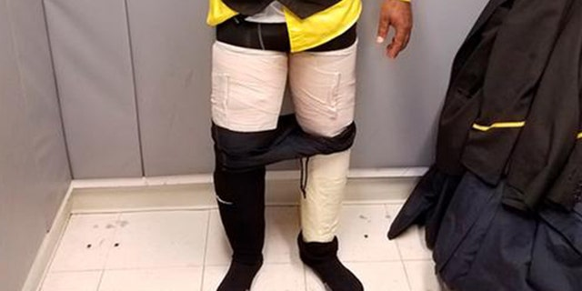 Customs officers discovered four packages containing white powder taped to an airline crew member's legs.