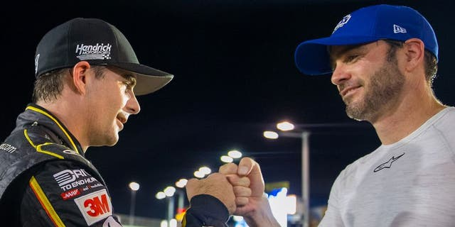 Nov 20, 2015; Homestead, FL, USA; NASCAR Sprint Cup Series driver Jeff Gordon (left) fist bumps teammate Jimmie Johnson following qualifying for the Ford Ecoboost 400 at Homestead-Miami Speedway. Mandatory Credit: Mark J. Rebilas-USA TODAY Sports