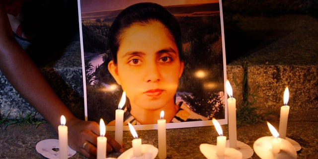 Dec. 13, 2012: A student of a nursing college places a candle in front of a picture depicting nurse Jacintha Saldanha, during a candle-lit vigil organized by a local politician in Bangalore, India.