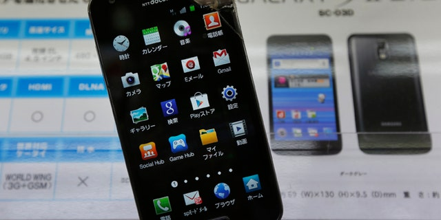Aug. 31, 2012: An electronic store staff shows a Galaxy S II LITE in Tokyo.