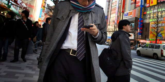 A young man uses a cell phone in a street in Tokyo Friday, March 4, 2011. Japan is engaging in soul-searching after police arrested a 19-year-old accused of cheating on a prestigious university's entrance examination by using his mobile phone to post questions on a popular online forum and get outside help.