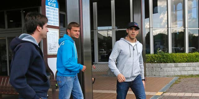 Lotus driver Pastor Maldonado of Venezuela, right, leaves a hospital where Marussia Formula One driver Jules Bianchi receives medical treatment in Yokkaichi, central Japan, Monday, Oct. 6, 2014. French driver Bianchi is in critical condition after crashing at the grand prix Sunday. Bianchi was unconscious when he was taken to the hospital following a crash during Sunday's rain-shortened race and is undergoing emergency surgery after a scan revealed a severe head injury.(AP Photo/Shuji Kajiyama)