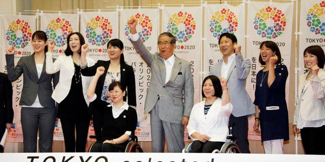 May 24, 2012: Tokyo Gov. Shintaro Ishihara, center, chairman of Tokyo 2020 Council, shows his spirit with Japanese Olympians and Paralympians during a press conference in Tokyo.