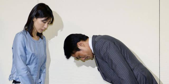 """Tokyo city assemblyman Akihiro Suzuki bows to his female counterpart Ayaka Shiomura for an apology at Tokyo Metropolitan City Hall in Tokyo Monday, June 23, 2014. Suzuki from Prime Minister Shinzo Abe's ruling party apologized for throwing one of several sexist hecklings at Shiomura Monday, five days after officials scrambled to identify the voices heard during her speech. A voice from the floor said """"You are the one who should get married first,"""" followed by laughter and more hecklings including """"She must be single"""" and """"Can't you have babies?"""" as Shiomura asked Tokyo's maternity support measures.  (AP Photo/Kyodo News) JAPAN OUT, CREDIT MANDATORY"""