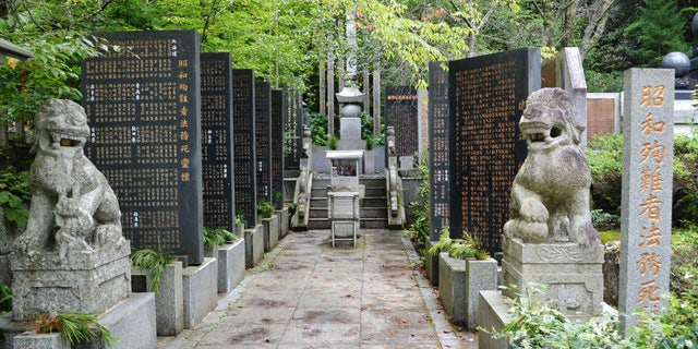 August 27, 2014: Stone-carved guardian dogs sit at the entrance of a memorial compound honoring World War II-era war criminals in Koyasan Okuno-in temple in Koya town, Wakayama prefecture, central Japan. (AP Photo/Kyodo News)
