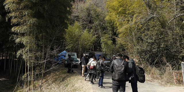 Journalists gather near the site where a body part believed to be of a missing woman was found in Osaka, western Japan Monday, Feb. 26, 2018.