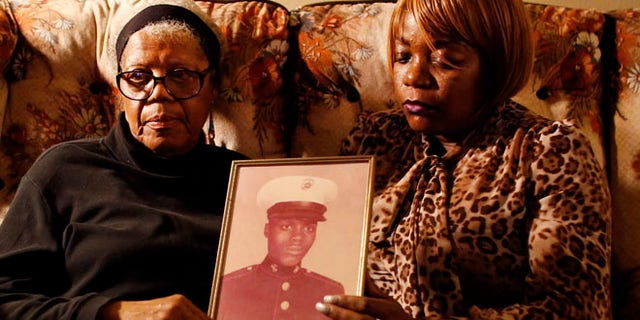 March 12, 2014: Alma Murdough and her daughter Cheryl Warner hold a photo of Murdough's son, at her home in the Queens borough of New York.