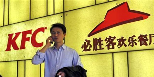 A man talks on his mobile phone in front of the logos of KFC and Pizza Hut, both restaurants under Yum Brands, in Shanghai, March 6, 2013. REUTERS/China Daily