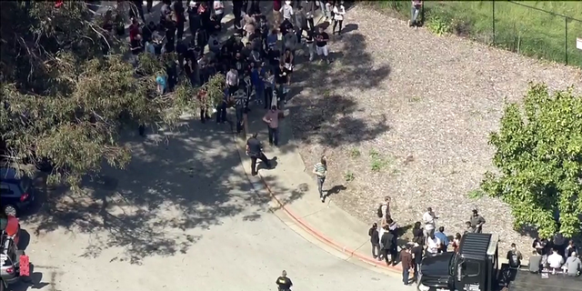 Aerial images showed officers on scene, with some patting down a line of people outside.