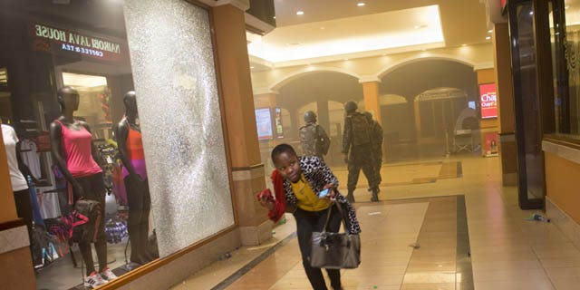 FILE - In this Saturday, Sept. 21, 2013 file photo, a woman who had been hiding during the gun battle runs for cover after armed police enter the Westgate Mall in Nairobi, Kenya, after gunmen threw grenades and opened fire at the upscale mall. (AP Photo)