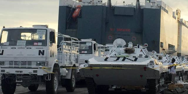 United Nations vehicles are offloaded from a Norwegian ship at the Kenyan port of Mombasa, Wednesday, Sept. 23, 2015. Kenyan security forces searching a Norwegian ship at Mombasa port discovered undeclared weapons among a consignment of U.N. vehicles, local police and the ship's Norwegian owner said Wednesday. (AP Photo)