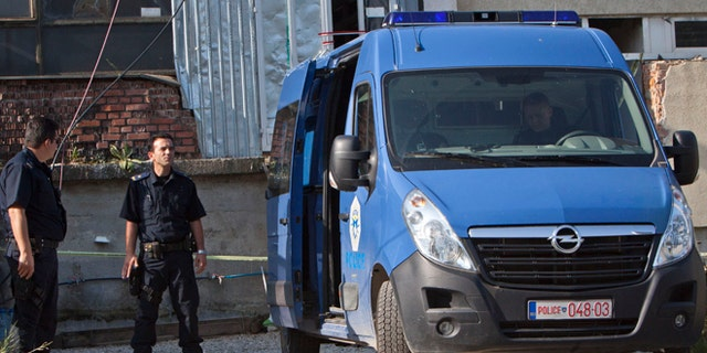 Aug. 11, 2014: Kosovo police officers guard the entrance of a makeshift mosque after a raid in Kosovo's capital Pristina. Kosovo police arrested at least 40 people in a major operation targeting Islamic radicals suspected of fighting alongside extremists in Iraq and Syria.