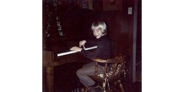 In this undated photo provided by Kim Cobain, a young Kurt Cobain plays piano in his childhood home in Aberdeen, Wash.