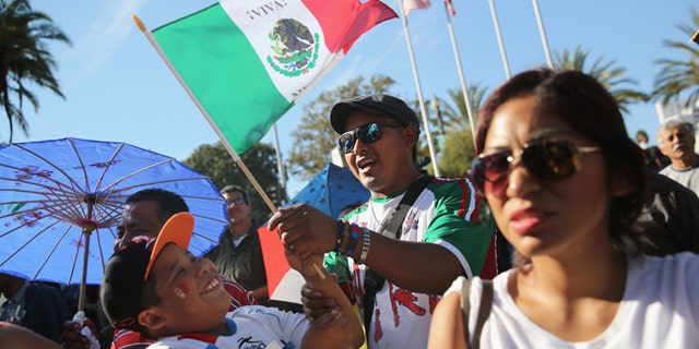 LOS ANGELES, CA - OCTOBER 06:  People sing the Mexican national anthem during the opening ceremony of the sixth annual Mole Fair on October 6, 2013 in Los Angeles, California. Thousands of people turned out to taste mole sauce recepies from the Mexican states of Oaxaca and Puebla for what's billed as the largest Mexican food festival in the United States. Los Angeles has the largest Mexican-origin population of any city in the world after Mexico City. (Photo by John Moore/Getty Images)