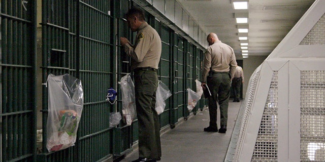 """FILE - In this Oct. 3, 2012, file photo, Los Angeles County Sheriff's deputies inspect a cell block at the Men's Central Jail in downtown Los Angeles. Federal officials say 18 current and former Los Angeles County sheriff's deputies saw themselves as being """"above the law,"""" engaging in corruption and civil rights abuses that included beating inmates and visitors, falsifying reports, and trying to block an FBI probe of the nation's largest jail system. (AP Photo/Reed Saxon, File)"""