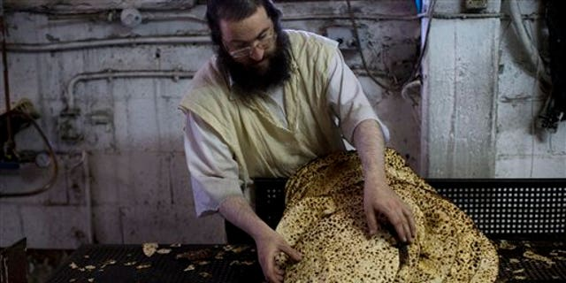 An Orthodox Jewish man prepares special matzoh, a traditional handmade Passover unleavened bread, at a bakery in Bnei Brak near Tel Aviv, Israel. Tuesday, March 31, 2015. (AP Photo/Oded Balilty)