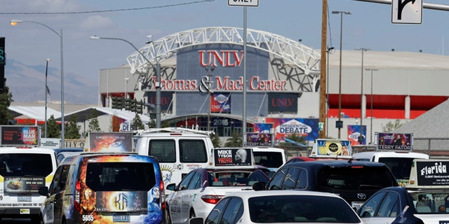 Cars drive along a road near the UNLV campus, Monday, Oct. 17, 2016, in Las Vegas. Traffic will be a major issue along the Las Vegas Strip and near UNLV as streets and a freeway close for security during the presidential debate at UNLV on Wednesday. (AP Photo/John Locher)