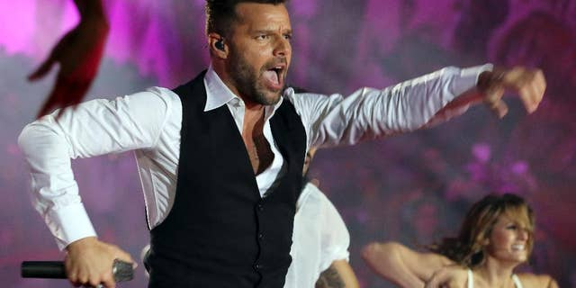 """FILE - In this May 31, 2014 file photo, Ricky Martin performs during the opening ceremony of the Life Ball in front of City Hall in Vienna, Austria. Televisa announced Thursday, July 24, 2014, that Martin will be a coach in the fourth season of """"La Voz...Mexico,"""" or """"The Voice...Mexico,"""" which premieres September 7. The Puerto Rican singer was previously a coach on the Australian version of """"The Voice."""" (AP Photo/Ronald Zak, File)"""