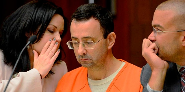 Defense attorney Shannon Smith talks to her client, Dr. Larry Nassar, during the second portion of his preliminary hearing on sexual assault at the 55th District Court in Mason, Mich.