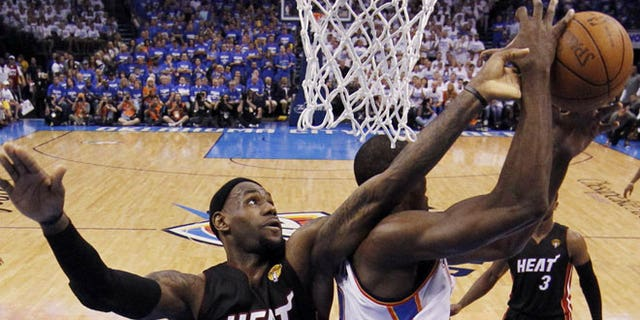 June 14, 2012: Miami Heat small forward LeBron James and Oklahoma City Thunder power forward Serge Ibaka (9) from Republic of Congo go after a loose ball during the first half at Game 2 of the NBA finals basketball series  in Oklahoma City.