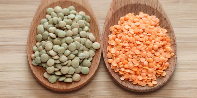 Green and red lentils in a wooden spoons. Close-up.