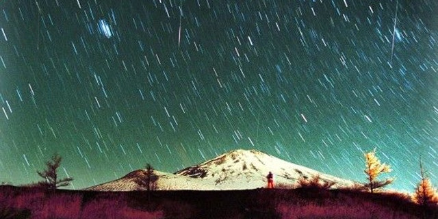 Leonid meteors are seen streaking across the sky over snow-capped Mount Fuji, Japan's highest mountain.
