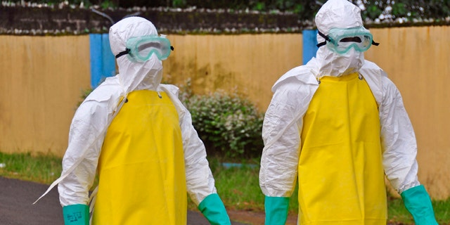 August 16, 2014: Health workers wearing protective gear go to remove the body of a person who is believed to have died after contracting the Ebola virus in the city of Monrovia, Liberia. (AP Photo/Abbas Dulleh)