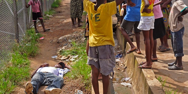 August 19, 2014: Children surround a man, left, who fell down while walking on a street suspected of having contracted the Ebola virus in the city of Monrovia, Liberia. The World Health Organization says the outbreak has killed more than 1,200 people, while authorities struggle to contain its spread and treat the sick. (AP Photo/Abbas Dulleh)