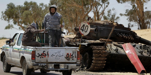 April 10, 2011: Rebel fighters armed with rocket propelled grenade launchers head back into Ajdabiya, past a previously destroyed pro-Gadhafi forces tank, during heavy shelling there, in Libya.