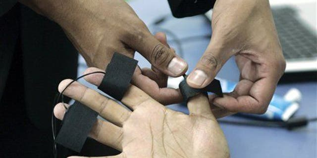 A polygraph examiner applies electrodes on the fingers of a subject.