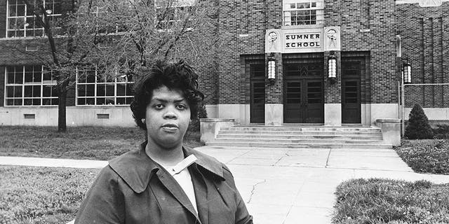 Linda Brown Smith stands in front of the Sumner School in Topeka, Kan., on May 8, 1964. The refusal of the public school to admit Brown when she was nine years old because she was black, led to the Brown v. Board of Education of Topeka, Kansas.