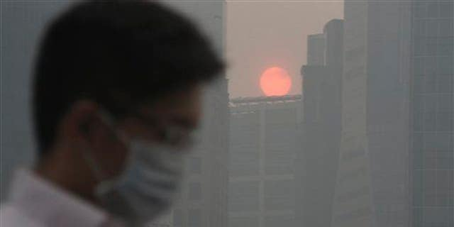 In this June 20, 2013 file photo, a masked man walks as the sun sets among buildings covered with haze, as Singapore urged people to remain indoors amid unprecedented levels of air pollution.